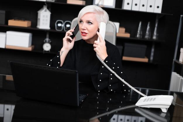 Beschäftigte frau, die auf dem mobile und überlandleitung bei tisch sitzen im büro spricht
