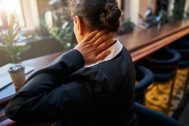 Beschäftigte frau, die ihren arbeitsplatz anschaut, während sie während des online-meetings eine pause macht und ihren nacken massiert