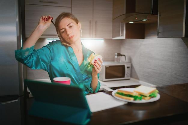 Beschäftigte frau, die isst, kaffee trinkt, am telefon spricht, gleichzeitig am laptop arbeitet. geschäftsfrau, die mehrere aufgaben erledigt