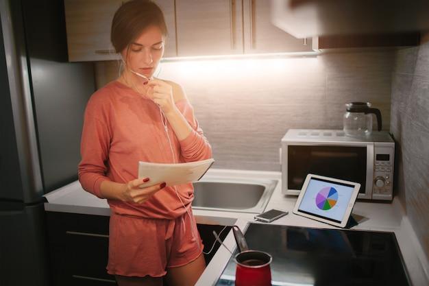 Beschäftigte frau, die kaffee zubereitet, am telefon spricht und gleichzeitig am tablet arbeitet. geschäftsfrau, die mehrere aufgaben erledigt. multitasking-unternehmer. freiberufler arbeitet nachts.