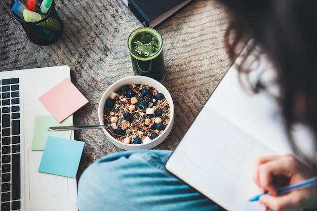 Beschäftigte frau, die mit dokumenten und laptop auf dem boden arbeitet, der müsli und frischen gemüsesaft isst
