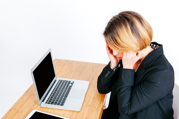 Beschäftigte frau, die unter kopfschmerzen leidet