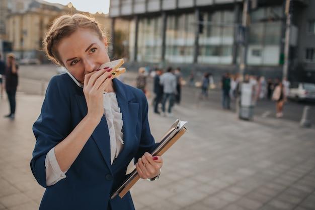 Beschäftigte frau hat es eilig, sie hat keine zeit, sie wird unterwegs einen snack essen. arbeiter essen, kaffee trinken, gleichzeitig telefonieren. geschäftsfrau, die mehrere aufgaben erledigt.