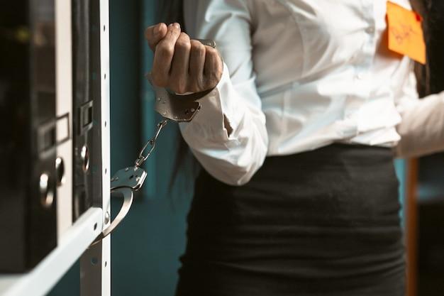 Beschäftigte frau im büro mit handschellen gefesselt