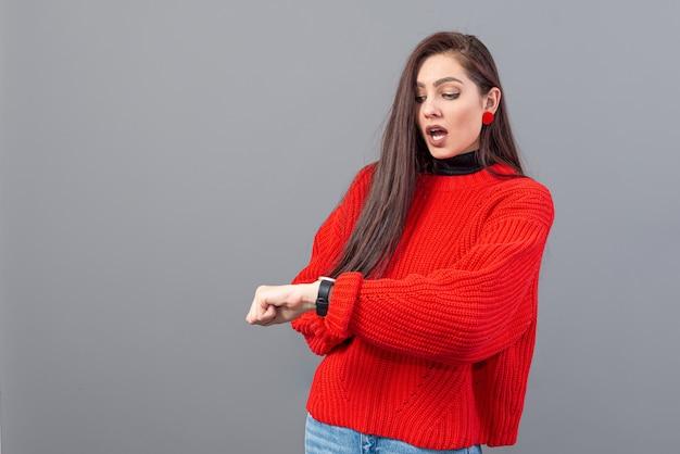 Beschäftigte frau in rotem wetter besorgt besorgt auf ihre armbanduhr, frau spät, isoliert auf grau