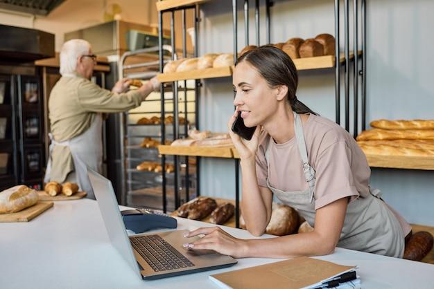 Beschäftigte frau in schürze, die laptop benutzt und kunden anruft