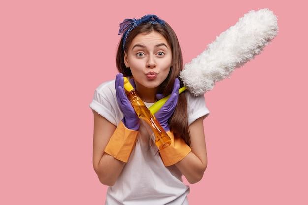 Beschäftigte frau macht grimasse, schmollt lippen, trägt kausale kleidung, hält pinsel und reinigungsmittel, macht frühjahrsputz