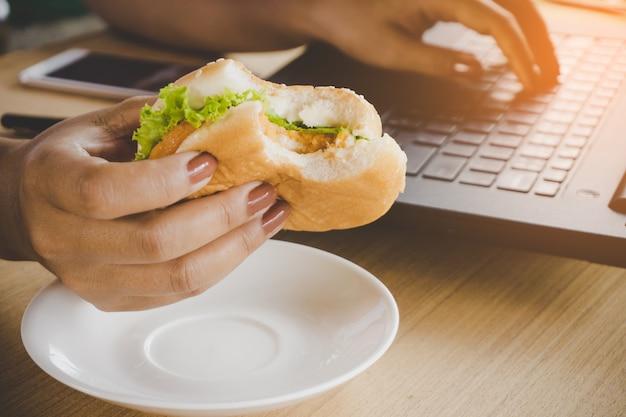 Beschäftigte frauarbeitskraft, die fertigkostburger beim arbeiten an laptop im büro isst