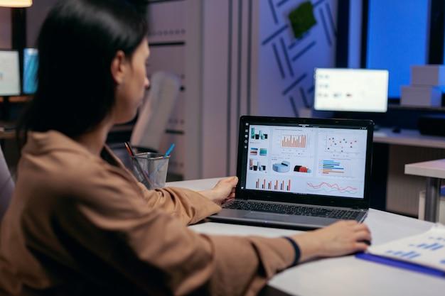 Beschäftigte geschäftsfrau, die an finanzberichten arbeitet, die statistikdiagramme überprüft und sich den laptop im laufe der frist ansieht. geschäftsfrau, die statistiken auf dem laptop-bildschirm betrachtet, der an ihrem arbeitsplatz sitzt