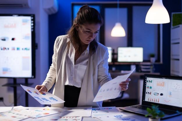 Beschäftigte geschäftsfrau, die auf finanzberichte schaut
