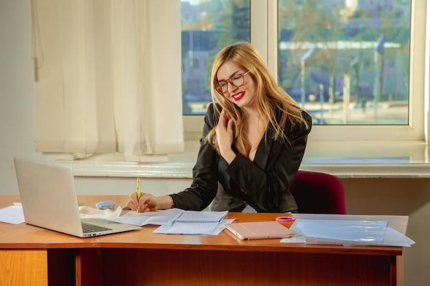 Beschäftigte geschäftsfrau sitzen im büro, benutzen einen laptop und sprechen auf dem handy. geschäftskonzept