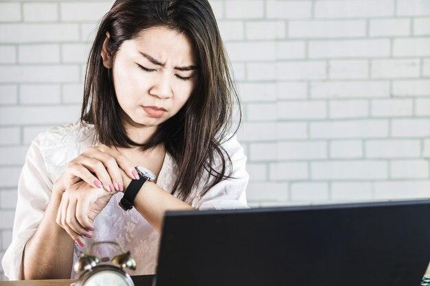 Beschäftigte geschäftsfrau, welche die zeit auf ihrer uhr überprüft