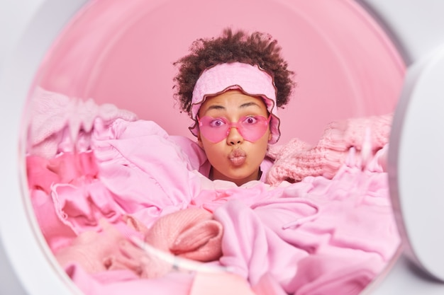 Beschäftigte hausfrau mit lockigen haaren hält die lippen gefaltet trägt eine trendige sonnenbrille lädt eine automatische waschmaschine, die in einem haufen kleidung über einer rosa wand vergraben ist