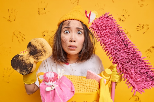 Beschäftigte hausfrau sieht mit gestresstem besorgtem ausdruck aus, dass die hausarbeit im haushalt reinigungsgeräte oder haushaltswerkzeuge in der nähe des wäschekorbs hält, isoliert auf gelber studiowand