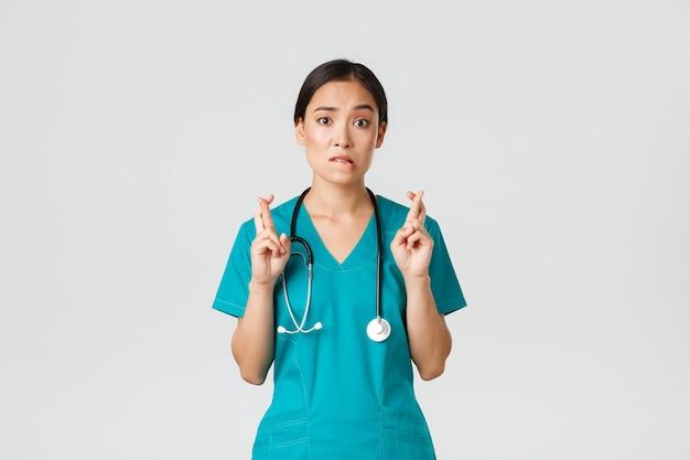 , beschäftigte im gesundheitswesen, pandemiekonzept. hoffnungsvolle nervöse asiatische praktikantin in peelings, die auf neuigkeiten warten, doktor daumen drücken und lippen beißen