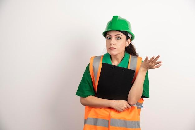 Beschäftigte ingenieurkonstrukteurfrau mit zwischenablage. foto in hoher qualität