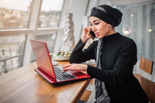 Beschäftigte junge arabische frau sitzen am tisch innen