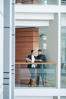 Beschäftigte junge büroangestellte in der abendgarderobe, die auf balkon im bürozentrum steht und tablette verwendet, während geschäftsplan bespricht
