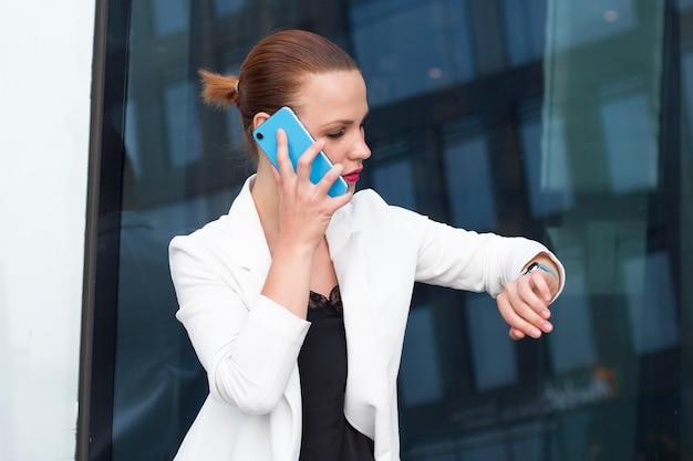 Beschäftigte junge erfolgreiche geschäftsfrau, die am handy spricht und ihre intelligenten armbanduhren betrachtet. überzeugte bürofrau, die um smartphone ersucht und zeit auf smartwatch überprüft.