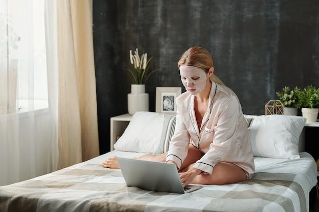 Beschäftigte junge frau im pyjama mit feuchtigkeitsspendender textilmaske im gesicht beim sitzen auf dem bett und beim stöbern im netz