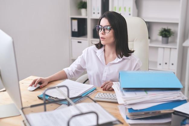 Beschäftigte junge frau in der bluse, die am schreibtisch sitzt und computer benutzt, während an stapel von dokumenten arbeitet