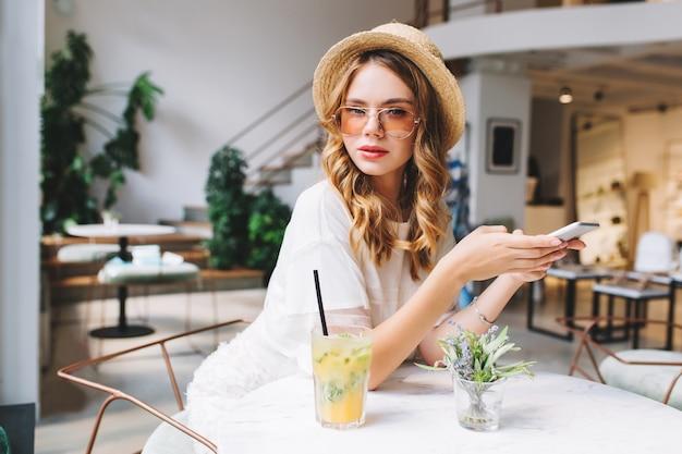 Beschäftigte junge frau in der trendigen brille und im weinlesehut, die auf anruf warten, während sie im gemütlichen café sitzen