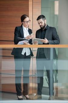 Beschäftigte junge kollegen in abendgarderobe, die im bürokorridor stehen und geräte synchronisieren, während sie dateien teilen