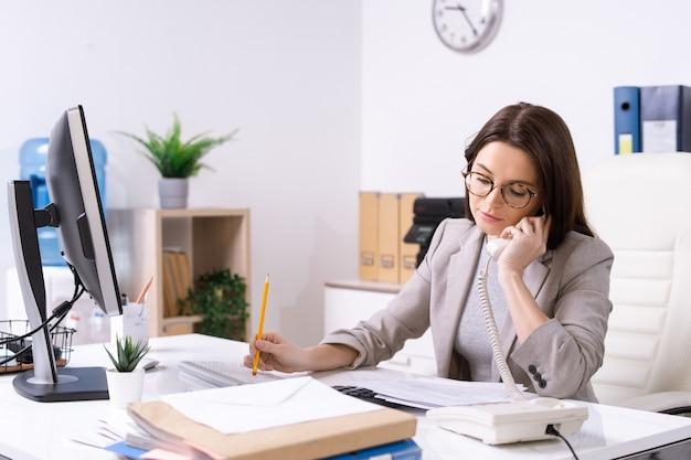 Beschäftigte junge sekretärin oder büroleiterin in abendgarderobe und brille, die am telefon spricht und durch papiere durch schreibtisch schaut