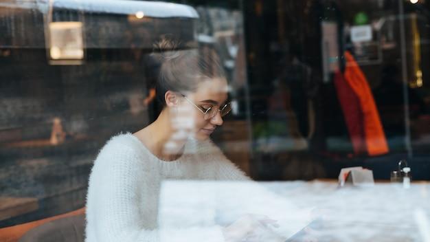 Beschäftigte junge studentin in einer weißen jacke und mit brille, die nach dem studium in einem café sitzt