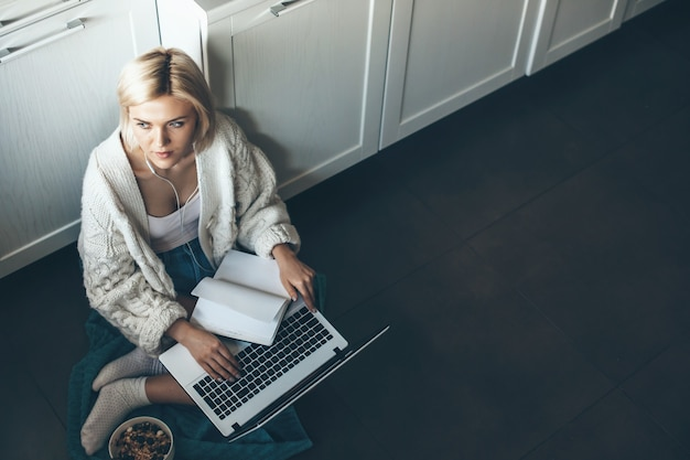 Beschäftigte kaukasische frau mit blonden haaren und kopfhörern, die am laptop mit einem buch arbeiten und müsli auf dem boden essen