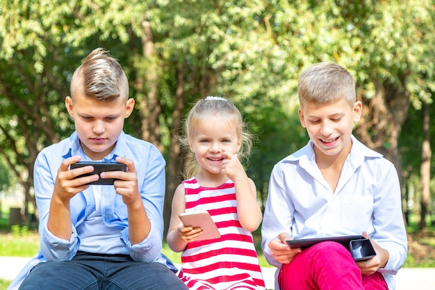 Beschäftigte kinder, die ihre telefone betrachten, die sms simsen und draußen sitzen spielen