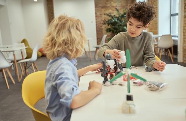 Beschäftigte kleine jungen, die während des stammunterrichts roboter untersuchen, die am tisch sitzen