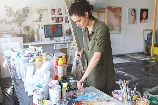 Beschäftigte malerin, die ölfarben nimmt, während sie in der nähe von tisch mit ölen steht, im kunststudio arbeitet und seelandschaft oder porträt zeichnet. attraktive junge frau, die auf leinwand an werkstatt arbeitet