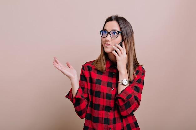 Beschäftigte moderne frau trägt brille, die auf smartphone mit wahren emotionen os isolierte wand spricht