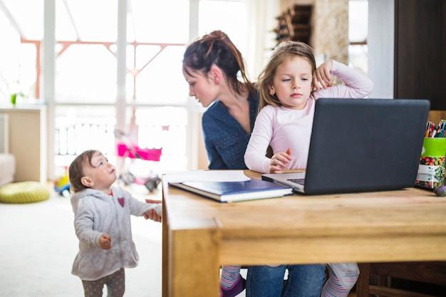Beschäftigte mutter, die ihr baby betrachtet