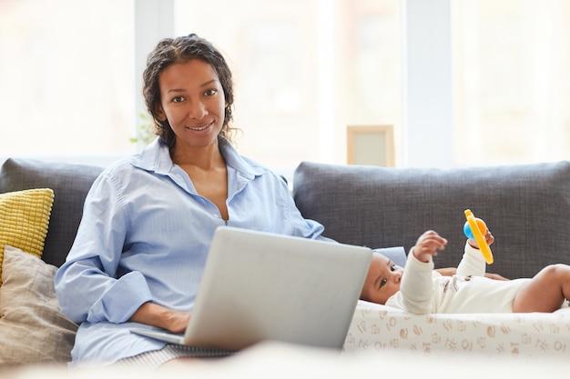 Beschäftigte mutter, die mit laptop arbeitet
