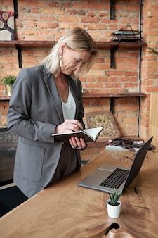 Beschäftigte reife dame in der jacke, die am schreibtisch im eigenen büro steht und zeitplan im planer überprüft