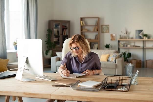 Beschäftigte reife frau in brille und freizeitkleidung, die notizen macht oder punkte des arbeitsplans vor computermonitor aufschreibt