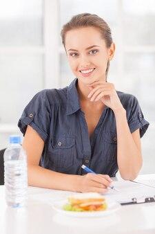 Beschäftigte schönheit. schöne junge frau, die etwas in ihren notizblock schreibt und lächelt, während sandwich und eine flasche wasser auf dem tisch liegen