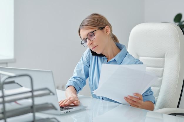 Beschäftigte sekretärin einer maklerfirma, die das telefon zwischen schulter und ohr hält, während sie mit dem kunden spricht, sich vernetzt und mit papieren arbeitet