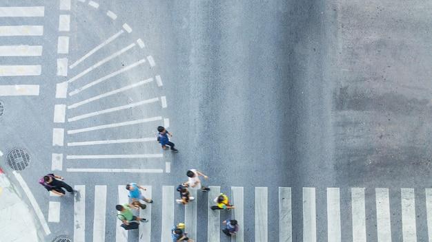 Beschäftigte stadtmenschenmenge bewegen sich zum fußgängerübergang auf verkehrsstraße