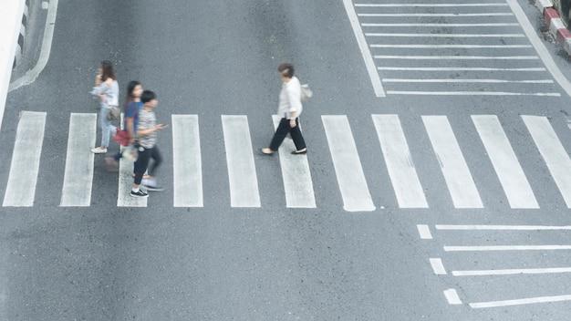 Beschäftigte unschärfenleute gehen schnell über das zeichen der kreuzung in der stadtstraße.