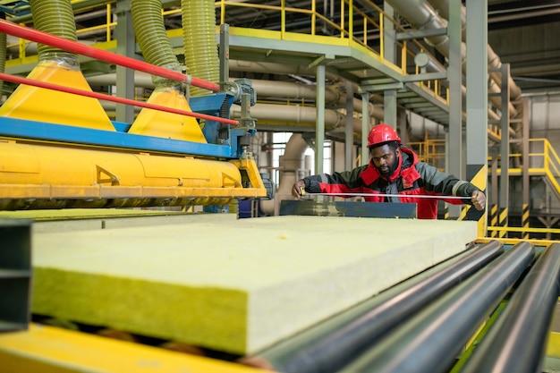 Beschäftigter afroamerikanischer arbeiter im roten helm unter verwendung des maßbandes beim überprüfen der größe der steinwolle auf dem förderband