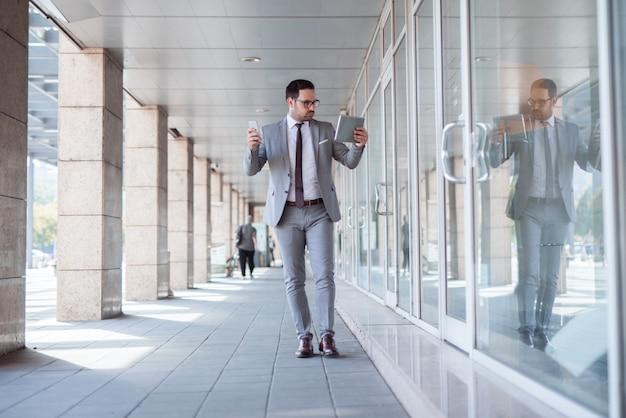 Beschäftigter angestellter, der auf der straße mit tablette in einer hand und smartphone in der anderen geht.