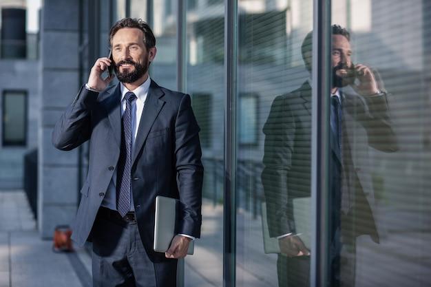 Beschäftigter arbeiter. angenehmer erwachsener büroangestellter, der am telefon spricht, während er einen laptop hält
