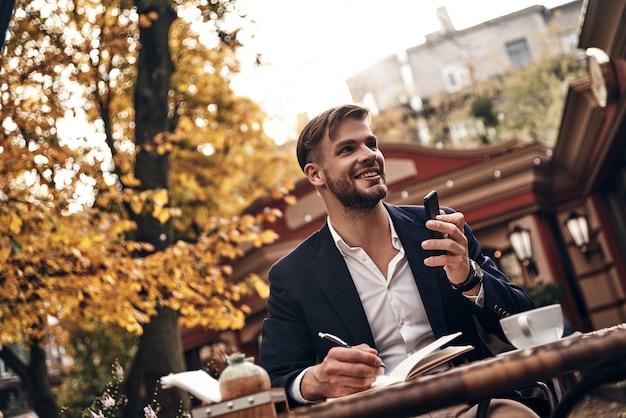 Beschäftigter arbeitstag. gut aussehender junger mann in eleganter freizeitkleidung, der sein smartphone hält und lächelt, während er im restaurant im freien sitzt