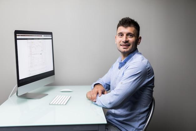 Beschäftigter arbeitstag. junger bärtiger händler, der mit laptop arbeitet, während er in seinem modernen büro vor computerbildschirmen mit handelstabellen sitzt.