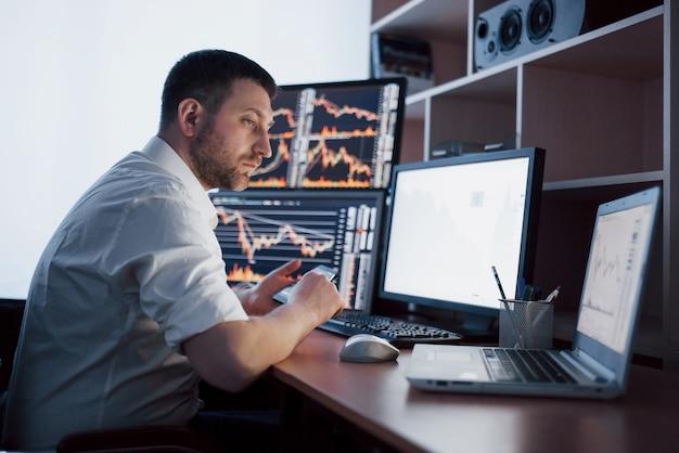 Beschäftigter arbeitstag. nahaufnahme des jungen geschäftsmanns, der monitor beim sitzen am schreibtisch im kreativen büro betrachtet.