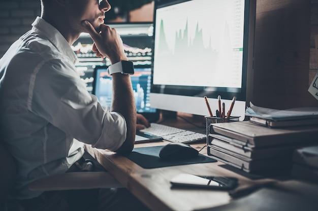 Beschäftigter arbeitstag. nahaufnahme eines jungen geschäftsmannes, der auf den monitor schaut, während er am schreibtisch im kreativbüro sitzt