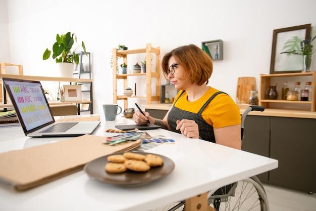 Beschäftigter behinderter junger webdesigner mit kurzen haaren, die im rollstuhl sitzen